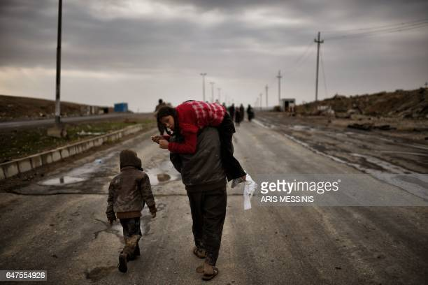 TOPSHOT An Iraqi man carries a girl as they walk down a road to flee Mosul on March 3 during an offensive by security forces to retake the western...