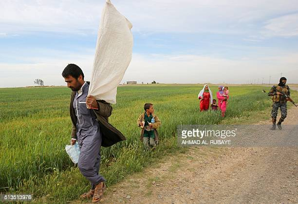 TOPSHOT An Iraqi man carries a makeshift white flag as he flees with his family a military operation by Iraqi security personnel aimed at retaking...