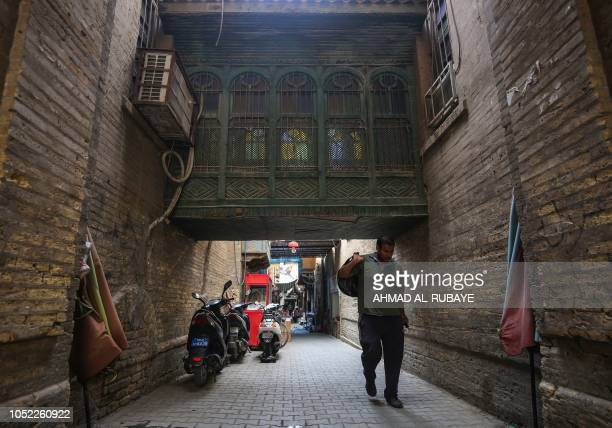 An Iraqi man carries a sack while walking down an old alley in the capital Baghdad on October 16 2018