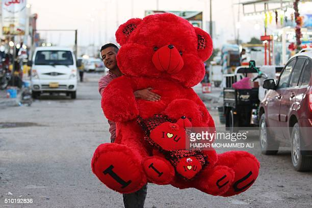 An Iraqi man carries a Valentine's day gift on February 14 in the mainly Shiite southern city of Basra / AFP / HAIDAR MOHAMMED ALI