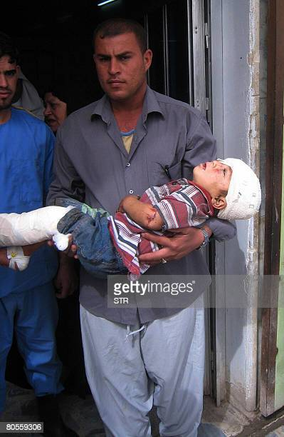 An Iraqi man carries a wounded boy in a hospital after he was wounded in a roadside bomb in Baquba on April 8 2008 A roadside bomb struck a passenger...