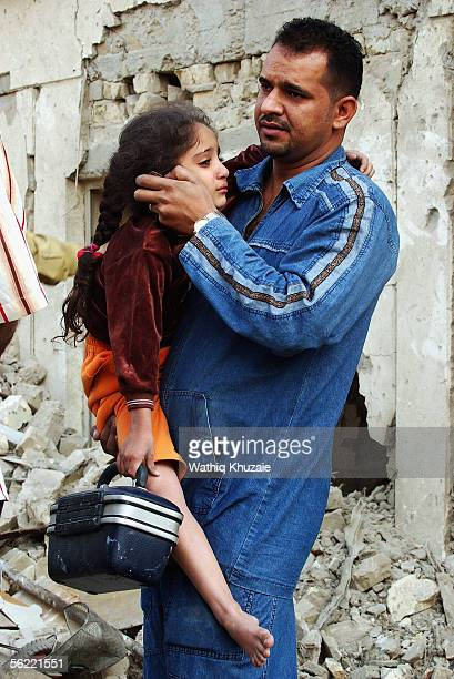 An Iraqi man carries his daughter from the site where two suicide car bombs exploded near an Interior Ministry building causing some nearby buildings...