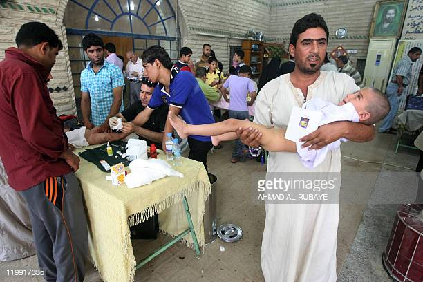 An Iraqi man carries his son after he was circumcised in Baghdad's impoverished district of Sadr city on July 15 2011 at the start of a twoday...