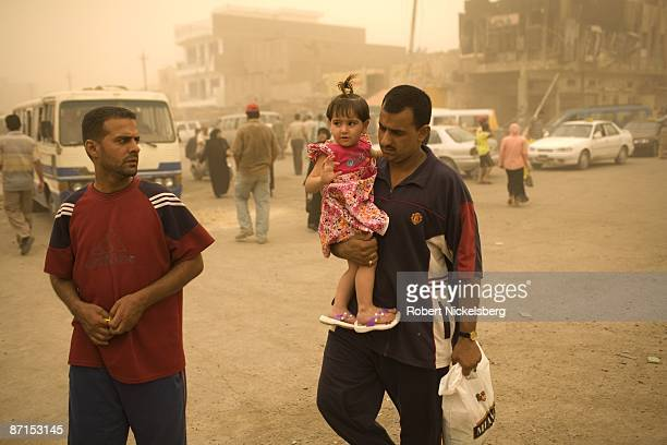 An Iraqi man carries his young child across the intersection of Al Quds and Fallah Streets in Sadr City the 25 million Shia dominated stronghold of...