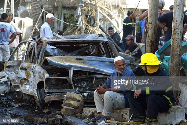 An Iraqi man chats with a fire fighter as they sit of the rubble of a building following a suicide bombing in the AlShab neighbourhood of Baghdad on...