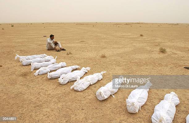 An Iraqi man checks a body list as sheets containing the remains of bodies excavated from a mass grave lie in the desert May 31 2003 on the outskirts...