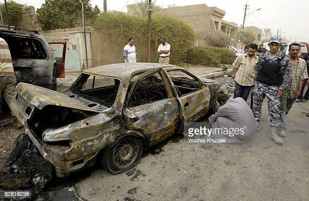 An Iraqi man checks his car burned in a car bomb explosion as others stand by at the site of a car bomb explosion on September 15 2008 in Karrada...