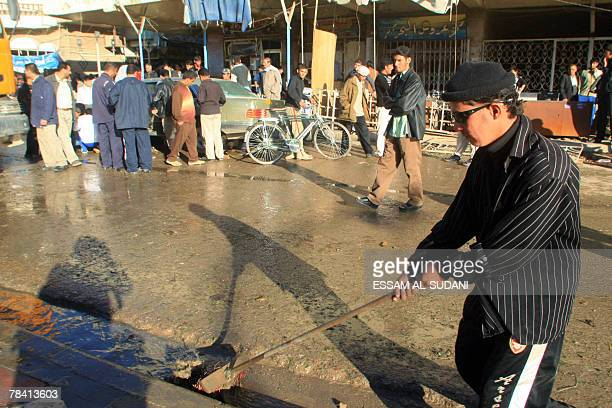 An Iraqi man cleans up the site of a car bomb in the southern Shiite city of Amara 12 December 2007 At least 28 people were killed and 151 wounded in...