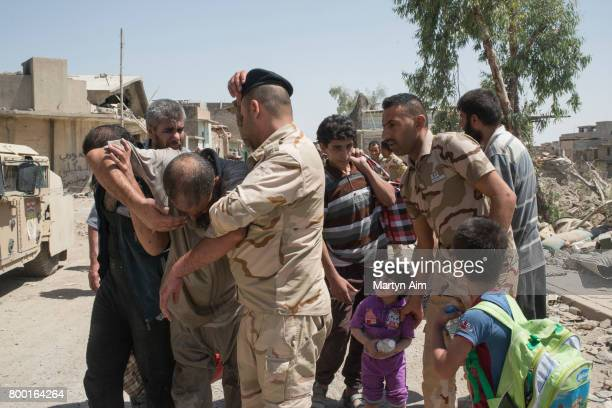 An Iraqi man collapses after fleeing the Islamic State controlled Old City of west Mosul where heavy fighting continues on June 23 2017 Iraqi forces...