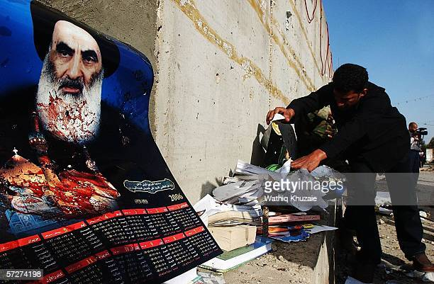 An Iraqi man collects the belongings of suicide bombings victims as a picture of the Powerful Shiite cleric Grand Ayatollah Ali al-Sistani is seen in...