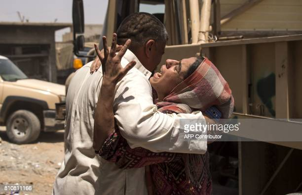 An Iraqi man comforts a relative who fled the fighting between government forces and Islamic State group jihadists in the Old City of Mosul as they...