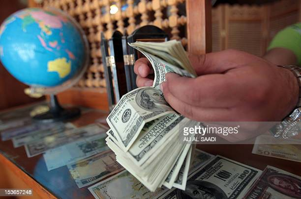 An Iraqi man counts money in his currency exchange bureau in Baghdad on April 11 as the price of goods went up across the country due to the new...