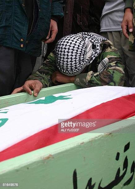 An Iraqi man cries over the coffin draped in the national flag prior to the funeral two brothers killed overnight in their village of Buhriz 5 kms...
