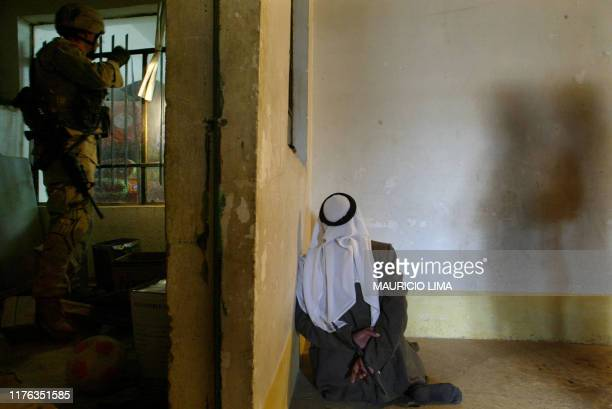 An Iraqi man detained and later released kneels on the ground as US soldiers inspect his house finding two fake rocketspropelled grenade during a...