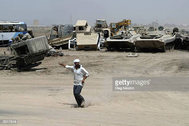 An Iraqi man directs the movement of trucks loaded with recovered artillery and tanks in a graveyard May 21 10 kmSouthWest of Baghdad Iraq US...