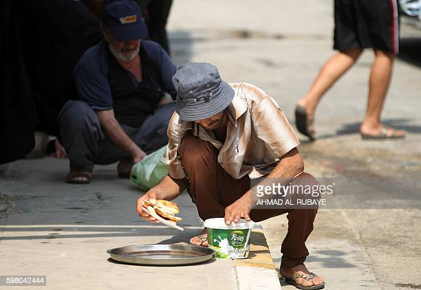 An Iraqi man eat on the pavement on August 31 2016 during a food distribution for displaced and impoverished families at the shrine of the Sunni...