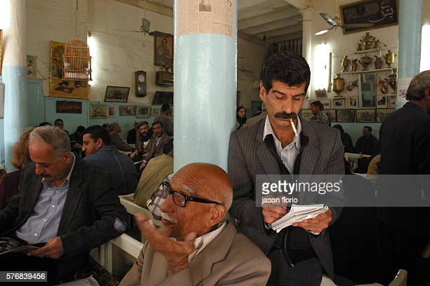 An Iraqi man engages in a discussion as another man writes in his notebook at the Sh'ah Bander cafe At the Sh'ah Bander cafe poets writers and...