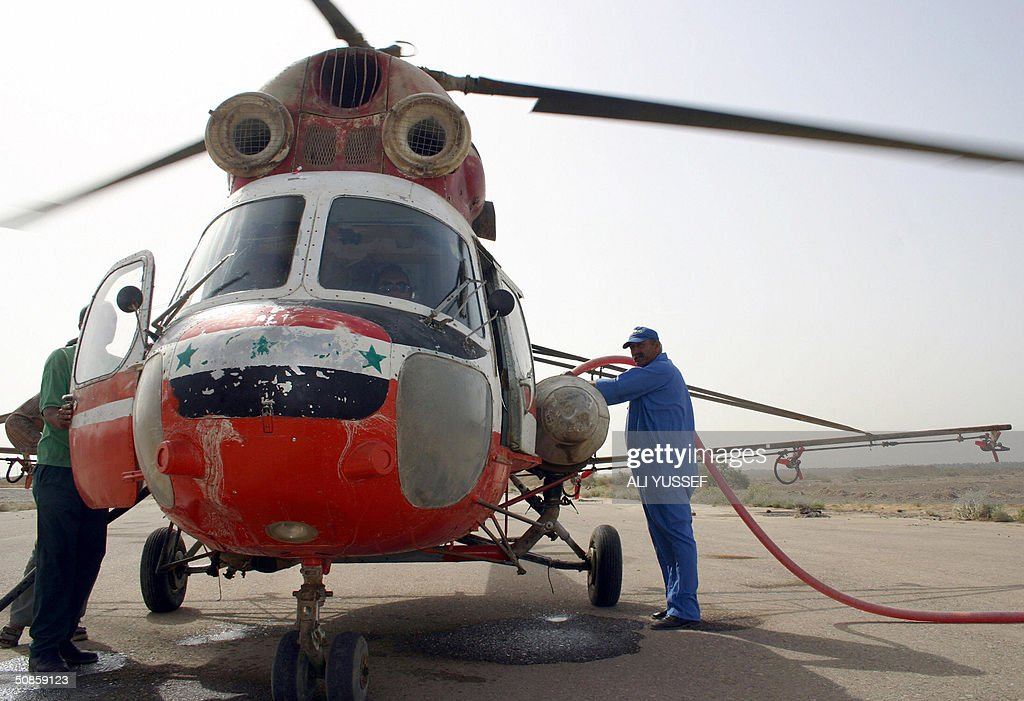 An Iraqi man fills a Russian-made MI-2 Iraqi helicopter with fuel before taking off to begin crop-dusting the date palm fields in the city of Baquba, northeast of Baghdad 20 May 2004. Iraqi pilots are flying again for the first time since the war started over a year ago, to spray date palm fields in a joint operation with coalition forces in eastern Iraq.