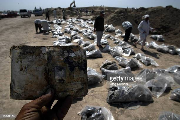 An Iraqi man holds an identification card found amongst bodies exhumed from a mass grave May 14 2003 in Mahaweel central Iraq Local residents dug up...