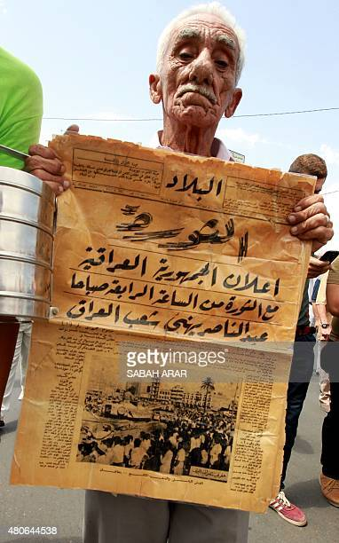 An Iraqi man holds an old copy of AlBilad Daily during a demonstration in the capital Baghdad on July 14 2015 organised by the Iraqi Communist Party...