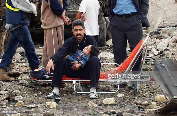 An Iraqi man holds his child at site where two suicide car bombs exploded near an Interior Ministry building causing some nearby buildings to...