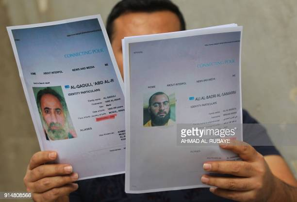An Iraqi man holds printed profiles of Abu Bakr alBaghdadi an his deputy Abd alRahman alQaduli released by Iraqi authorities on February 6 2018 Iraqi...