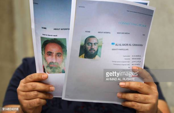 An Iraqi man holds printed profiles of Abu Bakr alBaghdadi an his deputy Abd alRahman alQaduli released by Iraqi authorities on February 6 2018 in...