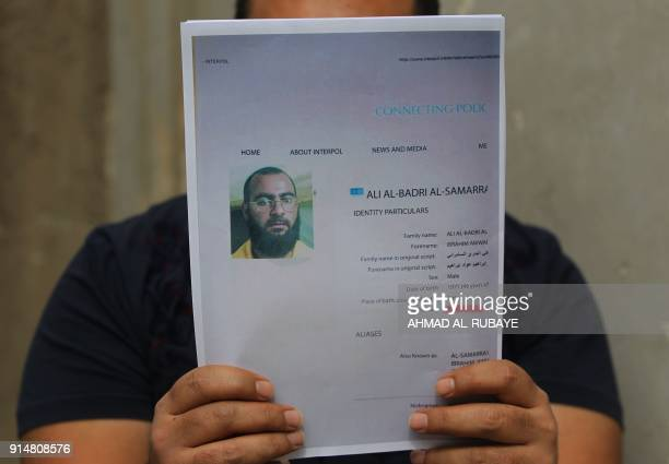 An Iraqi man holds printed profiles of Abu Bakr alBaghdadi released by Iraqi authorities on February 6 2018 Iraqi authorities issued a new list of...