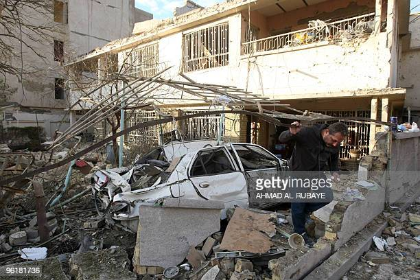 An Iraqi man inspects damages a day after a bomb blast near the Hamra Hotel in Jadriyah south of Baghdad on January 26 2010 Three huge and apparently...
