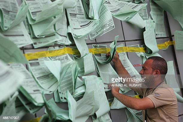 An Iraqi man inspects partial results which hang outside a vote counting centre in the capital Baghdad on May 8 following the country's general...