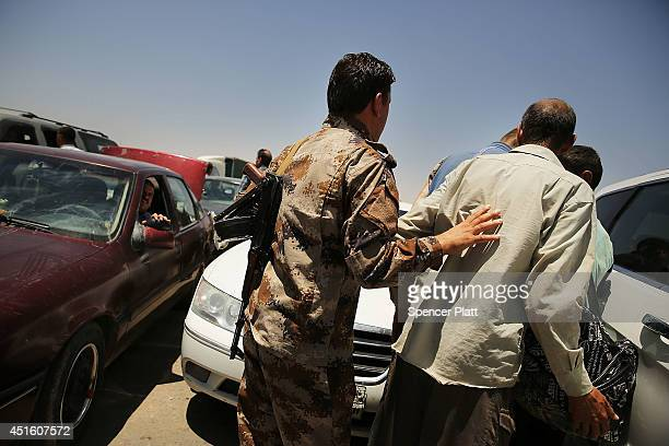 An Iraqi man is pushed away by a Kurdish soldier as Iraqis who have fled recent fighting in the cities of Mosul and Tal Afar try to enter a temporary...