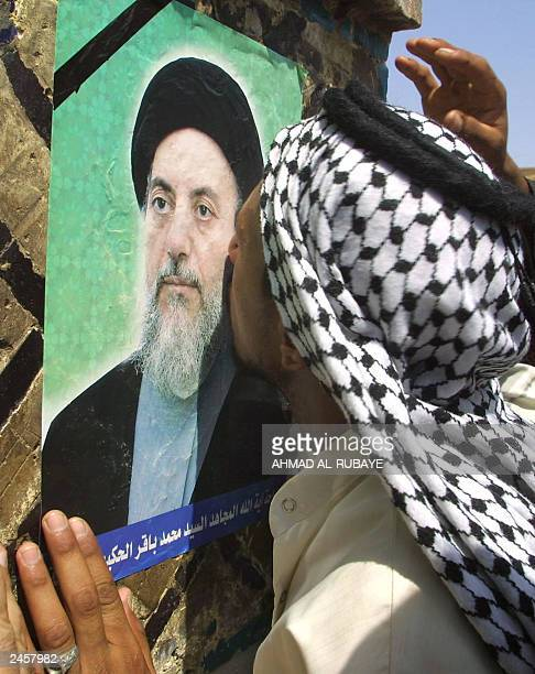 An Iraqi man kisses a poster of assassinated Ayatollah Mohammad Baqer alHakim at the Imam Ali shrine in the city of Najaf south of Baghdad 02...