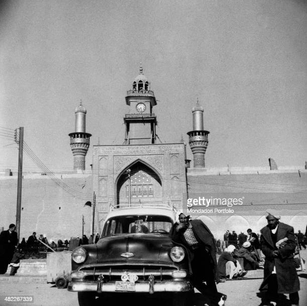 An Iraqi man leaning on a car and waiting in front of the Al-Kadhimiya Mosque also known as the Golden Mosque. Baghdad, December 1956
