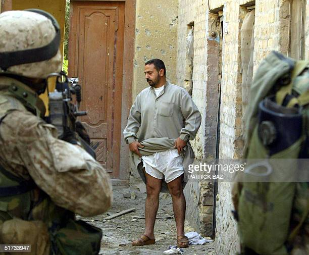An Iraqi man lifts his Galbiya to show US marines from the 3/5 Lima company that he has no hidden arms as they conduct a housetohouse search in the...