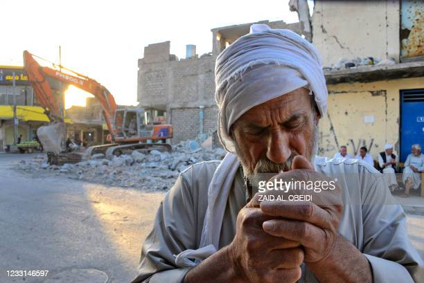 An Iraqi man lights a cigarette next to a building in the Iraqi city of Mosul, on May 26 that was destroyed during fighting with the Islamic State...