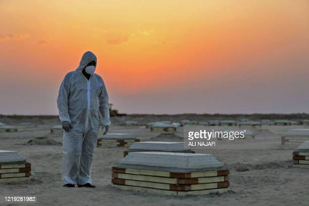 An Iraqi man looks at a tombstone at a cemetery for COVID-19 victims, 20 km from the central holy city of Najaf, on June 10, 2020.
