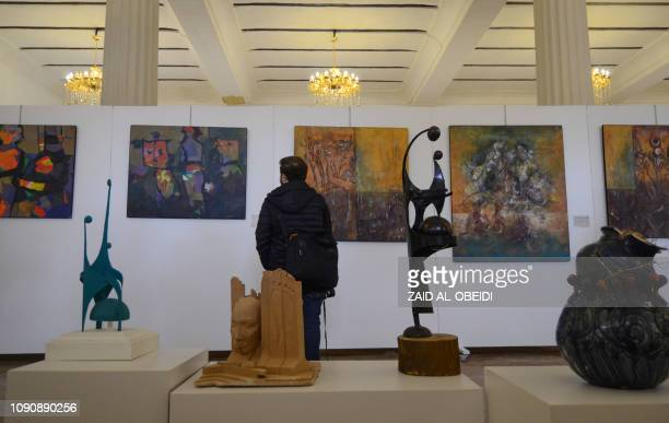 An Iraqi man looks at paintings on January 29 2019 at a contemporary art exhibition at one of the halls of the national museum of the northern Iraqi...