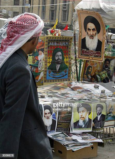 An Iraqi man looks at posters for sale of Shiite religious leaders outside the Imam Ali shrine in the holy city of Najaf 09 March 2004 Shiite...