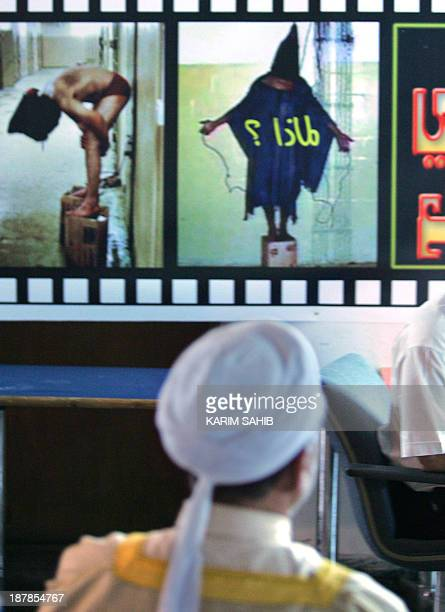 An Iraqi man looks at posters of published images showing Iraqi prisoners held in the notorious USrun Abu Ghraib prison close to the hall where an...