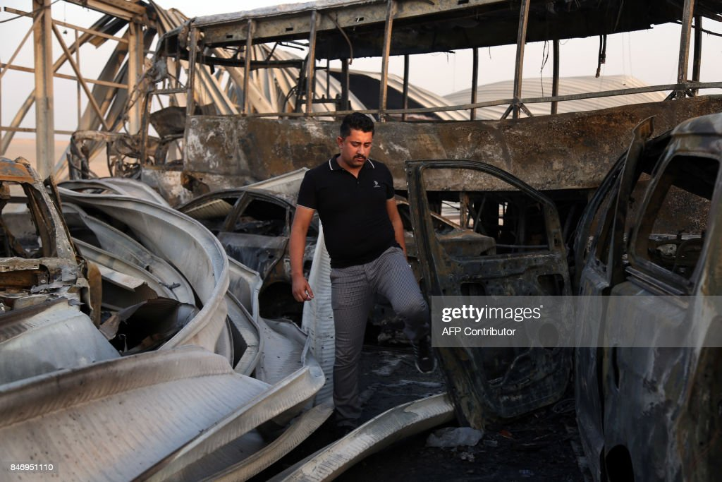 TOPSHOT - An Iraqi man looks at the damage after gunmen and suicide car bombers killed dozens of people in two assaults claimed by Islamic State (IS) group jihadists near the southern Iraqi city of Nasiriyah on September 14, 2017. The attackers struck at midday, opening fire on a restaurant before getting into a car and blowing themselves up at a nearby security checkpoint, officials said. / AFP PHOTO / Haidar HAMDANI