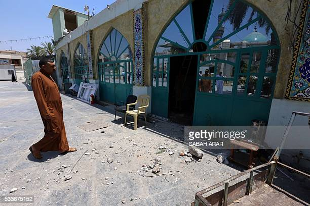 An Iraqi man looks at the damage after mortar fire hit the shrine of Sayyid Idris in Baghdad's central Karrada district without causing casualties on...