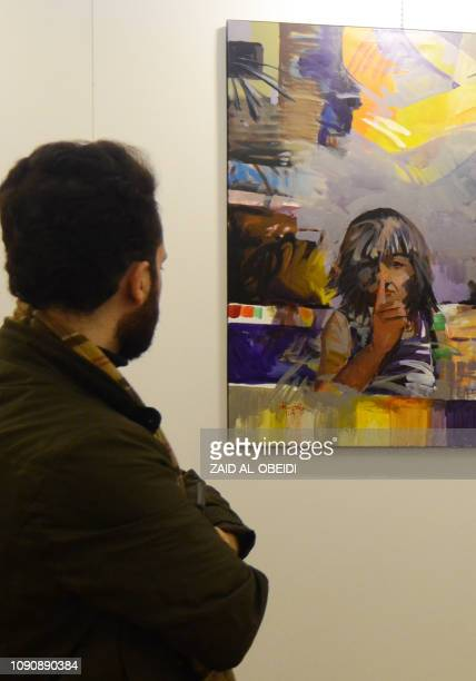 An Iraqi man looks on January 29 2019 at a painting displayed at a contemporary art exhibition hall in the museum of the northern Iraqi city of Mosul...