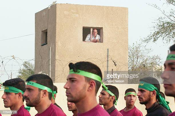 An Iraqi man looks out from his window as members of the alMehdi Army march during a military parade through the streets of the Sadr City...