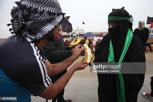 An Iraqi man offers a Shiite Muslim pilgrim a piece of fruit as she walks along the main highway between the cities of Nasiriyah to Samawa slowly...