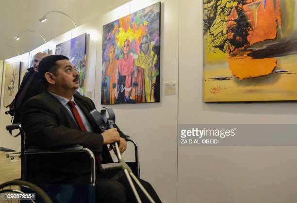 An Iraqi man on a wheelchair looks on January 29 2019 at paintings displayed at a contemporary art exhibition hall in the museum of the northern...