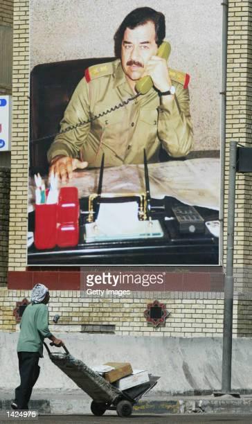 An Iraqi man passes a poster of President Saddam Hussein September 21 2002 in Baghdad Iraq Iraq said it would not follow UN resolutions threatening...