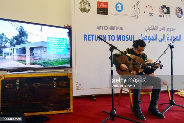 An Iraqi man plays the oud an oriental string instrument during the opening on January 28 2018 of an art exhibition at the national museum of the...