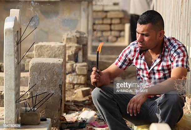 An Iraqi man prays next to the grave of a relative at the alGhazali cemetery in Baghdad on the first day of Eid alAdha on October 26 2012 Eid alAdha...