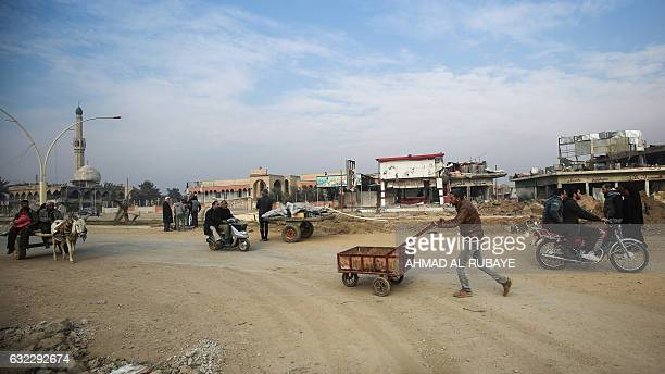TOPSHOT An Iraqi man pushes a cart in a street near the University of Mosul after government forces retook control of the area from the Islamic State...