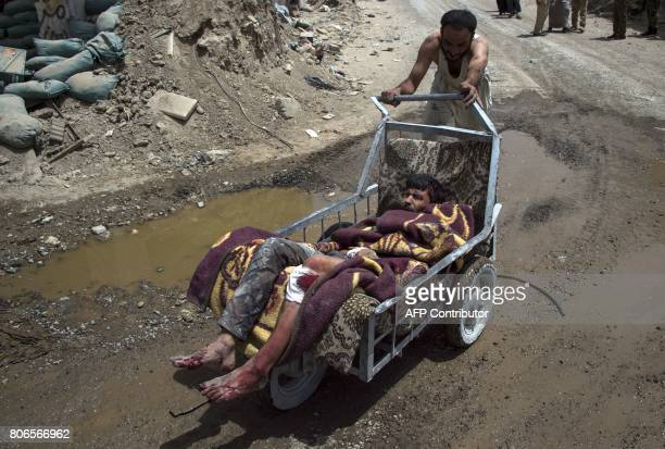 TOPSHOT An Iraqi man pushes an injured man on a cart as they evacuate civilians in the Old City of Mosul on July 3 2017 during an ongoing offensive...